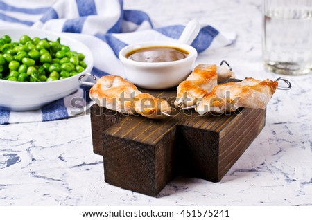 Grilled chicken on skewers with garnish of green vegetables. Selective focus. - stock photo