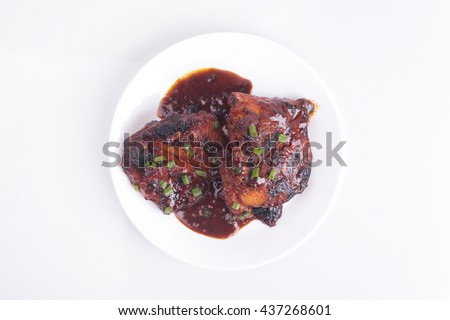Grilled chicken or ayam golek on white plate, white background. Malaysian traditional cuisine