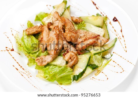 Grilled chicken salad with cucumber and lettuce. Isolated on white
