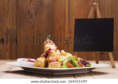 Grilled chicken skewers with pineapple, peppers and onions served with french fries and vegetable salad - stock photo
