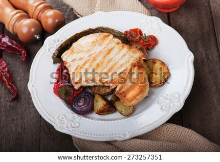 Grilled chicken steak with roasted potato and vegetables on wooden table - stock photo