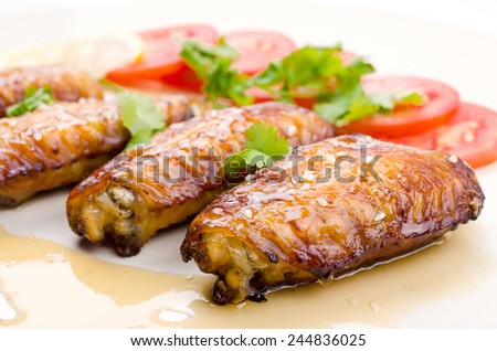 Grilled chicken wings and vegetables on white background - stock photo