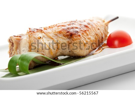 Grilled Chicken Wings Garnished with Cherry Tomato and Green Leaf
