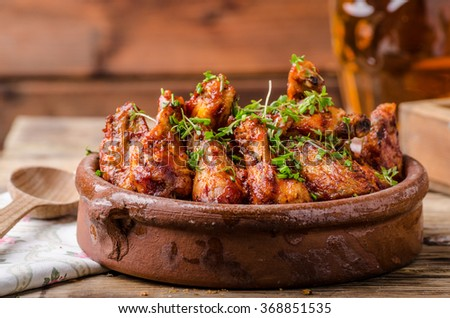 Grilled chicken wings in homemade Sriracha souce, topped with fresh microgreens, fresh beer behind - stock photo