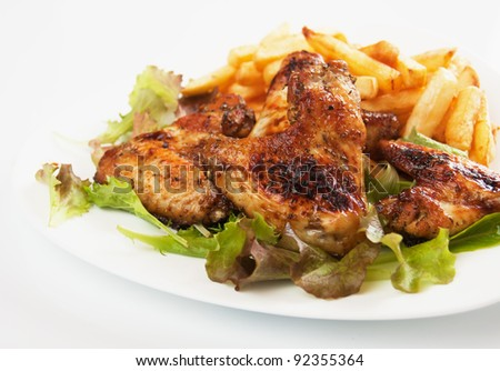 Grilled chicken wings served with french fries and lettuce - stock photo