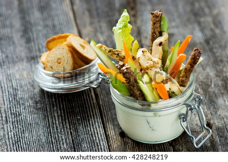 Grilled chicken wings with creamy sauce for dipping with a glass filled with sliced fresh vegetable  - stock photo