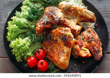 Grilled chicken wings with fresh vegetables. Baked chicken meat with lettuce and tomatoes cherry. Homemade meat on wooden table.  - stock photo