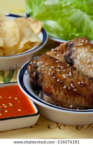Grilled chicken wings with hot pepper sauce and chips