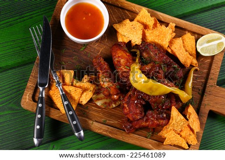 Grilled chicken with chips and jalapeno pepper on wood board with cultery top view - stock photo