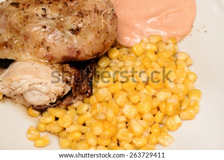 grilled chicken with corn and hot sauce on plate - stock photo