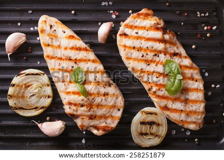 Grilled chicken with onion and garlic on the grill close up. horizontal view from above