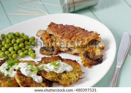 Grilled chicken with potato pancakes on a plate.