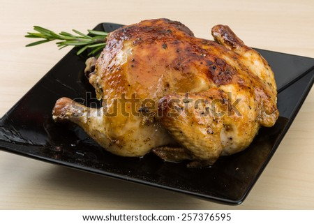 Grilled chicken with rosemary on the wood background - stock photo
