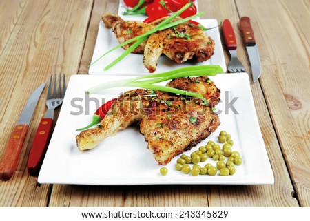 grilled chickens : grilled quarter chicken garnished with green sweet peas , and cutlery on white plates over wooden table - stock photo