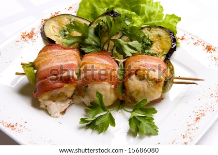 Grilled chiken meat wraped in bacon stringed on wooden brochette decorated with grilled egg-plant, leaves of salad and parsley on white plate - stock photo