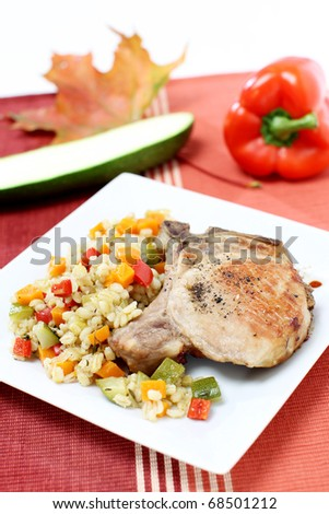 Grilled chop pork with barley and other vegetables - stock photo