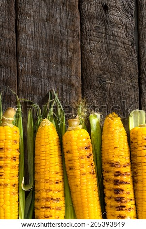 Grilled corn on the wooden table with blank space above - stock photo