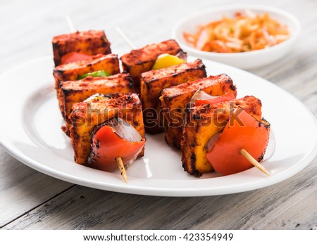 grilled cottage cheese or also known as Paneer Tikka Kebab or chili paneer or chilli paneer or tandoori paneer in india India, barbecued in red sauce, selective focus