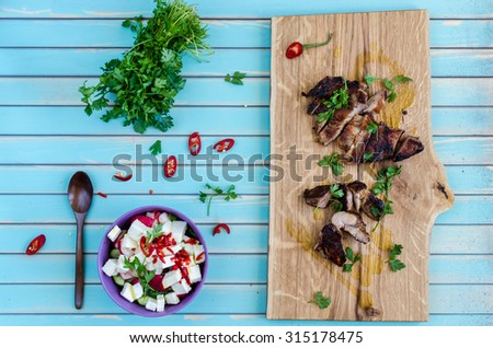 Grilled cutting pork steak on chopping board served with salad of radishes, cucumbers and fresh goat cheese with chili peppers and parsley, wooden spoon over rustic wooden turquoise table, top view - stock photo