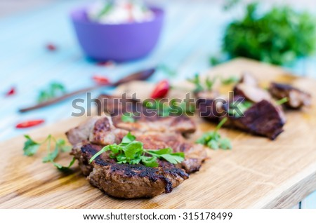 Grilled cutting pork steak on chopping board served with salad of radishes, cucumbers and fresh goat cheese with chili peppers and parsley around, wooden spoon over styled wooden turquoise table - stock photo