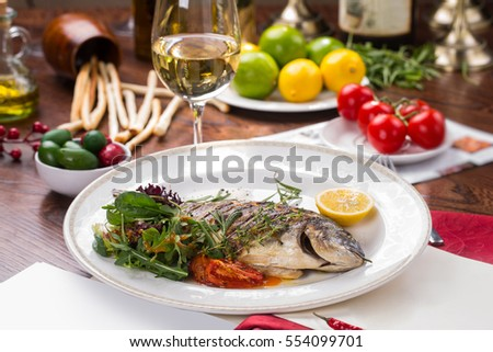 Grilled dorado fish in white table.