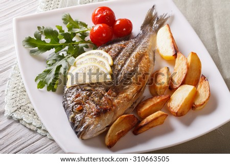 Grilled dorado fish with fried potatoes and lemon on a plate close-up. Horizontal