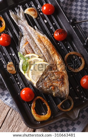 Grilled dorado fish with lemon and vegetables close-up on the grill pan. vertical top view - stock photo