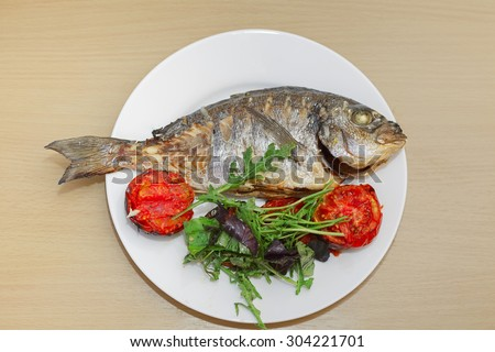 Grilled dorado fish with tomatoes, arugula and basil on white plate and wooden table