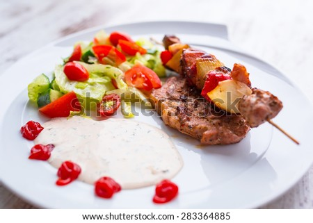 Grilled duck shashlik with salad on the plate - stock photo