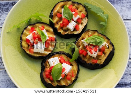 Grilled eggplant with feta cheese, red peppers and basil - stock photo