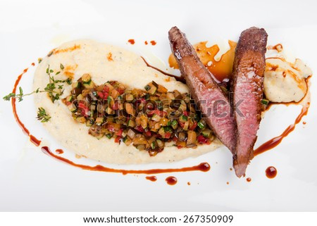 grilled fillet of lamb with creamy thyme polenta, vegetables and decorated with gravy - stock photo