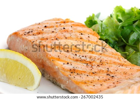 Grilled fillet of salmon on plate with green salad.