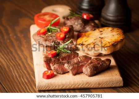 grilled fillet steak with tomatoes and roast vegetables on an old wooden board, background.