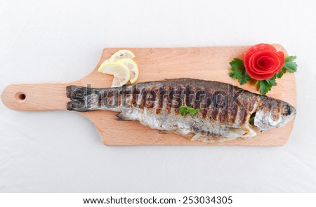 Grilled fish and vegetables on an wooden board - stock photo