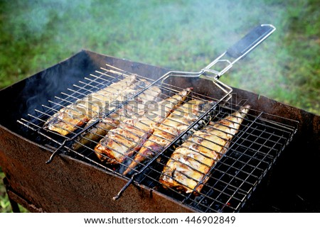 Grilled fish dish. Mackerel, cooked on the grill in the open air flow. Five fishes on the grill in the smoke, tasty and fresh food, picnic, party, outdoor recreation. - stock photo