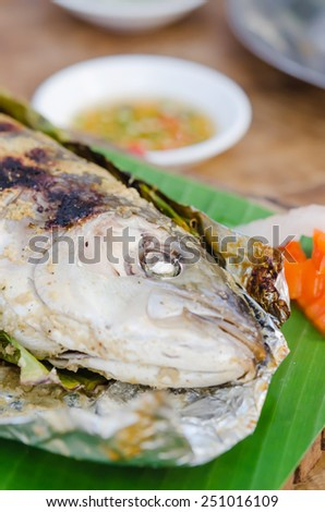 Grilled fish on green banana leaf with herbs - stock photo