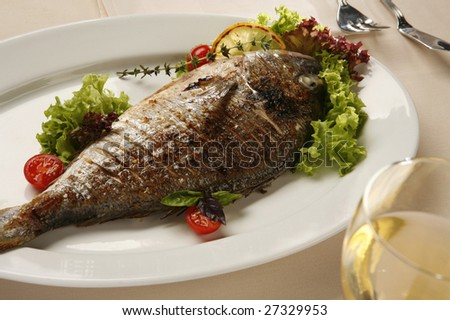 grilled fish on white plate with vegetables - stock photo