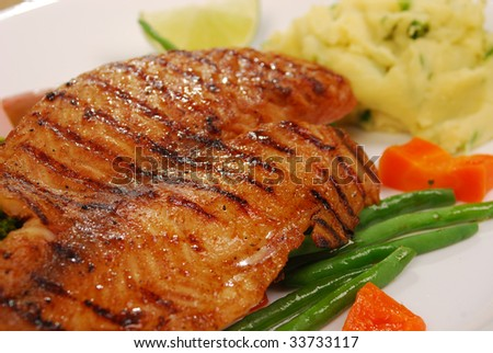 grilled fish with carrots, potatoes pure on white plate