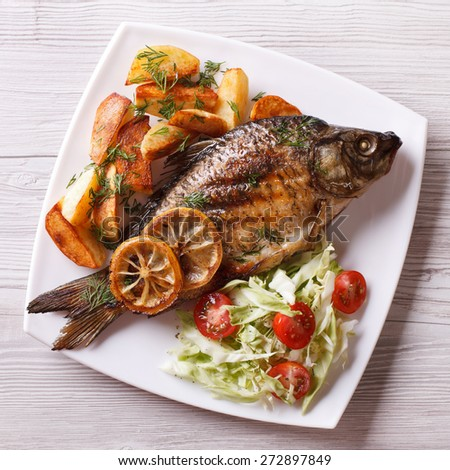 grilled fish with fried potatoes and salad on a plate. top view closeup  - stock photo
