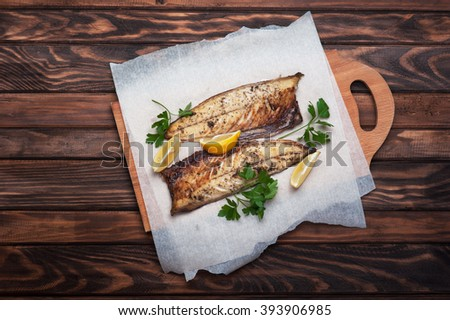 Grilled fish with herbs and lemon on rustic dark wooden background - stock photo