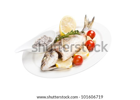 grilled fish with tomato, lemon and souse on plate with white background - stock photo