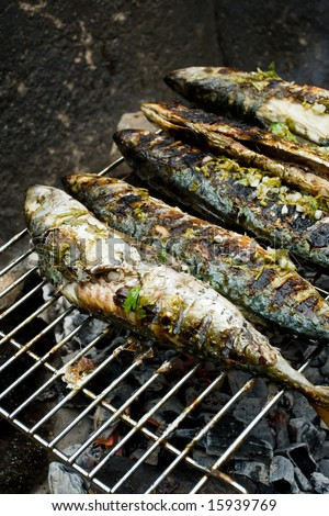 Grilled fishes laying on hot grill - stock photo