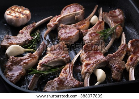 Grilled fresh lamb meat ribs with spices, garlic and rosemary in a pan grill - stock photo