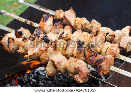 grilled fresh meat on skewers until golden brown - stock photo