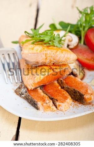 grilled fresh salmon filet with vegetables salad tomato arugula mushrooms and paprika on top - stock photo