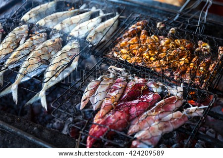 Grilled fresh seafood: prawns, fish, octopus, oysters food background Barbecue / Cooking BBQ seafood on fire / Indonesia - stock photo