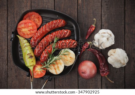 Grilled german sausages and vegetables in grilling pan - stock photo