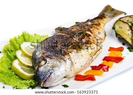Grilled gilt head sea bream on plate with lemon ,salad and grilled vegetables - stock photo