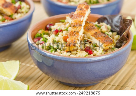 Grilled Halloumi and Tabbouleh - Salad made with bulghur wheat, tomato, parsley and pomegranate seeds topped with grilled halloumi. - stock photo