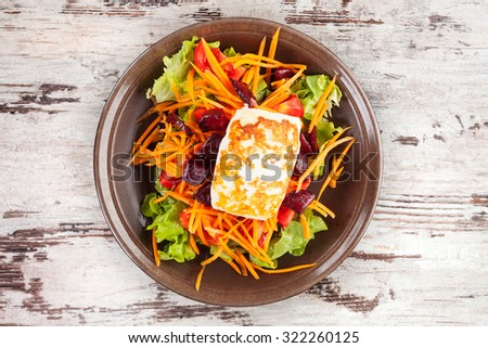 Grilled halloumi cheese with colorful fresh salad on plate on wooden table, top view. Culinary delicious vegetarian eating, mediterranean style. - stock photo